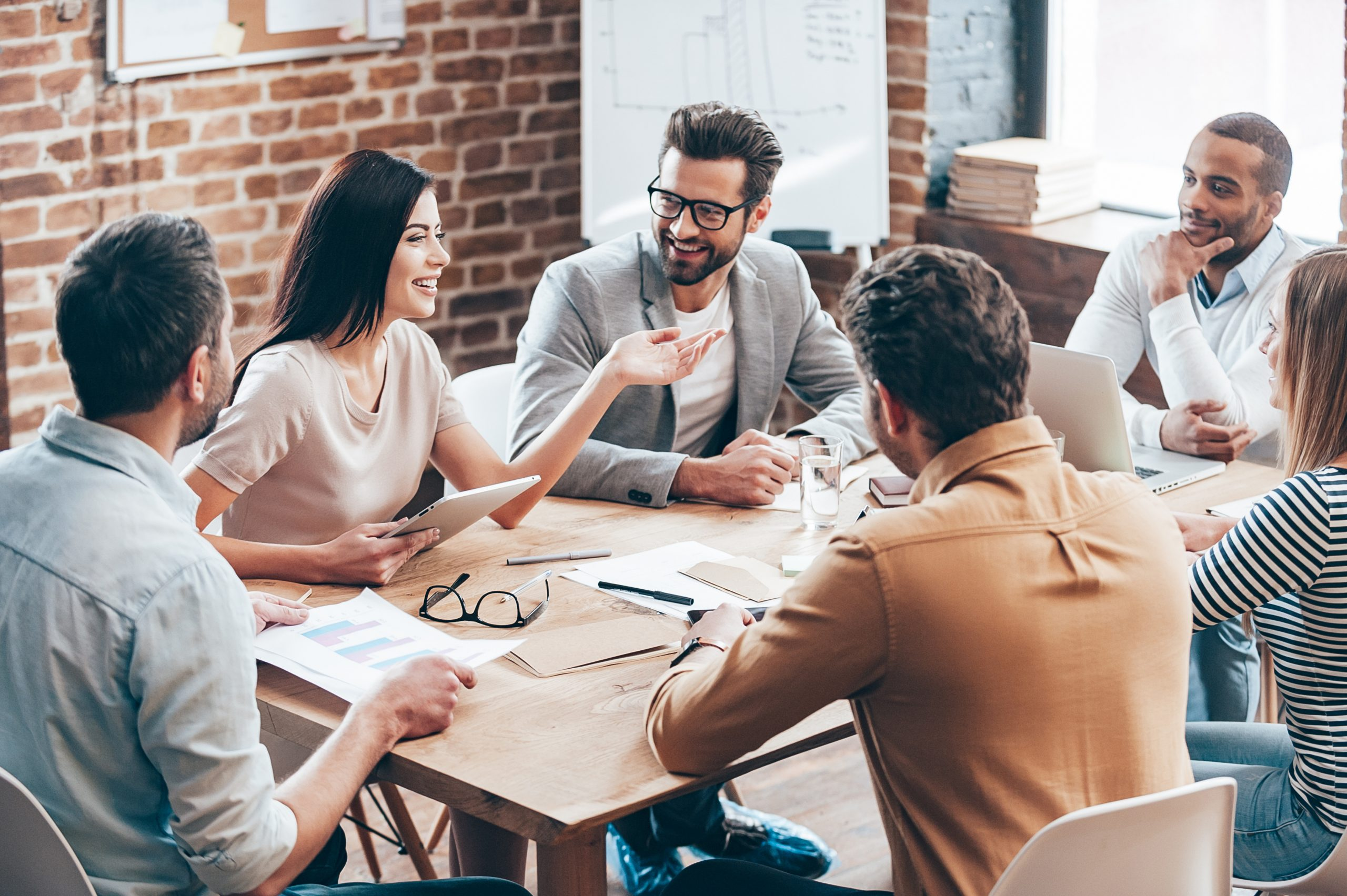 Team of Translation Business Professionals sitting around table in office collaborating on translation project Translation Solutions, San Diego, Let's Work Together, Free Quote, Contact Us, Call (858) 613-0936
