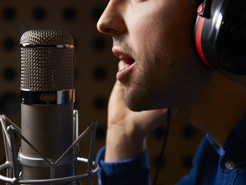Man with headphones speaking into microphone for voice-over talent project, Translation Solutions San Diego CA