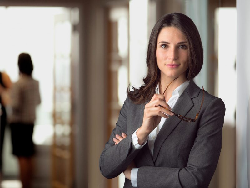 Female lawyer in dark gray business suit holding glasses in law firm office Translation Solutions San Diego