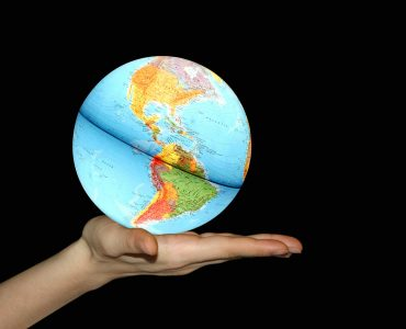 A colorful globe in hand on black background which is used as a company logo for Translation Solutions in San Diego